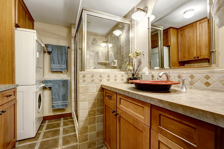 screened: Bathroom interior with tile trim, glass screened shower and laundry area