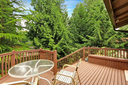 wooden railings: Wooden walkout deck with patio area overlooking backyard