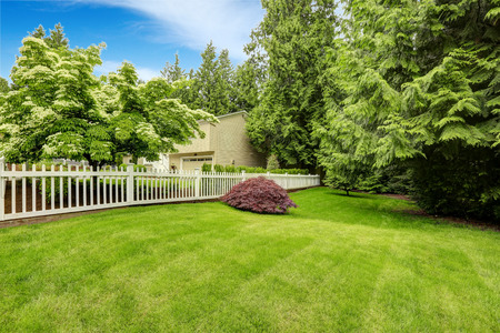Beautiful front yard landscape with white fence. Red bush on green lawn Standard-Bild