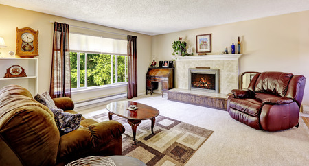 comfort room: Luxury living room with fireplace and antique elements. Comfortable leather chair and brown sofa create comfort