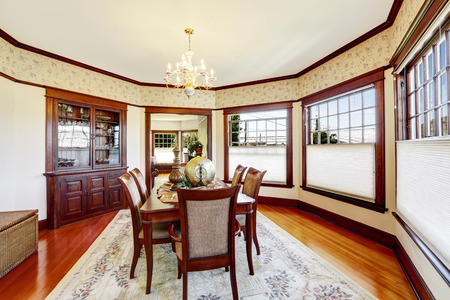 family dining: Luxury dining room with wood trim and built-in cabinet. Decorated family dining table .