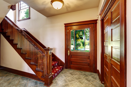 Entrance hallway with wooden staircase and red carpet covered steps