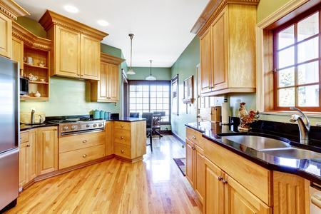 cabinets: Light green tone kitchen with wooden cabinets and hardwood floor