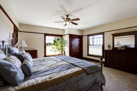 master bedroom: Master bedroom with iron frame bed and green tree in the corner