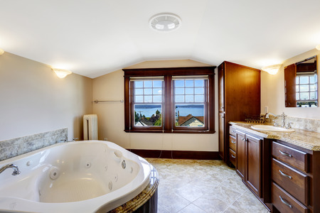 Luxury bathroom with whirlpool, brown cabinet and white whirlpool bath tub photo