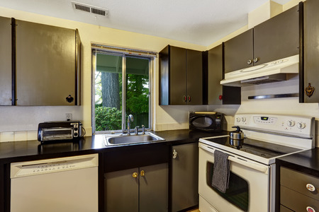 black appliances: Kitchen room in contrast white and black colors. Black cabinets refreshed with white appliances