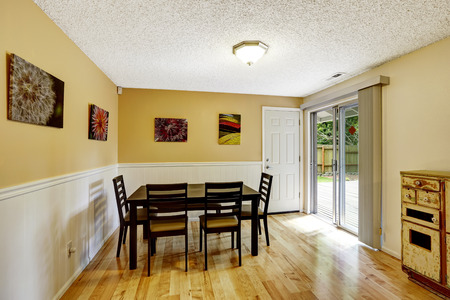 white trim: Dining room with light yellow walls and white trim. Simple black diing table set. Room has exit to backyard patio area Stock Photo