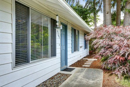 white trim: White house exterior with blue trim.. Entrance door and concrete walkway
