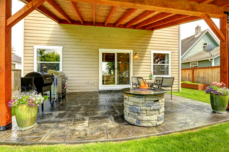 lawn area: Pergola with patio area. Tile floor decorated with flower pots. Stone trimmed fire pit, patio table set and barbecue Stock Photo