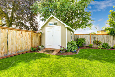 Beautiful new shed with flower bed on backyard area Archivio Fotografico