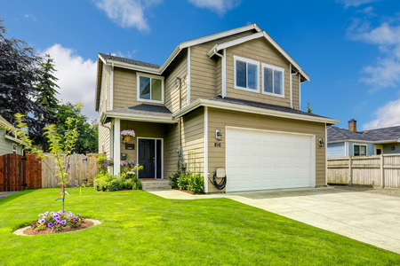 Two story house exterior with white door garage and driveway Imagens