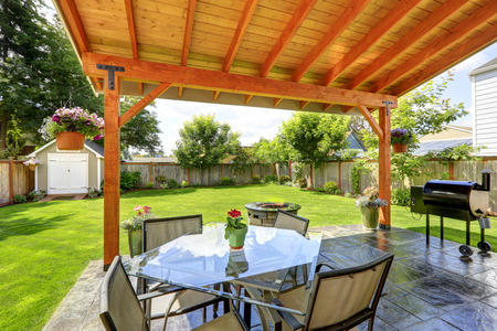 pergola: Pergola with patio area. Glass top table with chairs, fire pit and barbecue Stock Photo