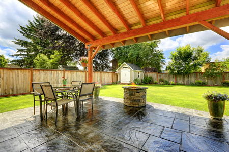 set in stone: Pergola with patio area. Tile floor decorated with flower pots. Stone trimmed fire pit and  patio table set