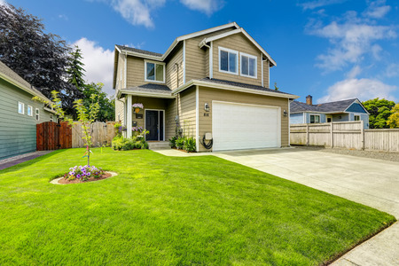 garage: Two story house exterior with white door garage and driveway Stock Photo
