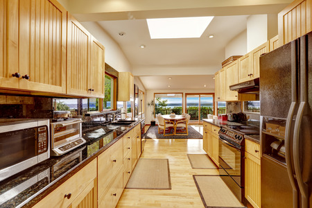 black appliances: Empressive kitchen room with black shiny couter tops and skylight. View of dining area with exit to walkout deck Stock Photo