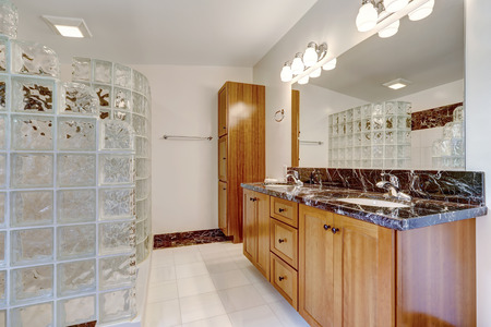 screened: Bathroom with glass block screened shower. Brown cabinet with black granite top and large mirror