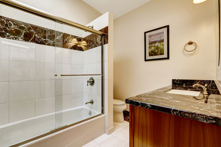 screened: Bathroom with glass screened bath tub. Brown cabinet with black granite top