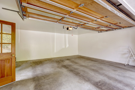 Spacious empty garage interior with open automatic door