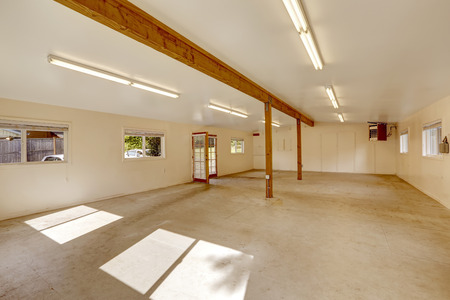 vaulted ceiling: Empty huge room of the shop working home studio with concrete floor and windows.