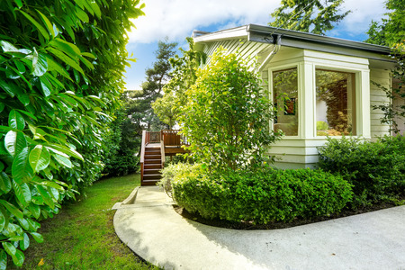 House with small walkout deck and concrete walkway. Beautiful green landscape
