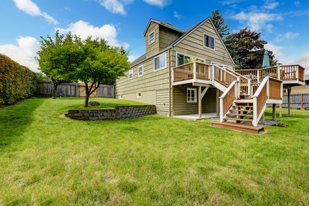white trim: Big house with walkout deck in brown and white trim. Spacious backyard area with trees Stock Photo