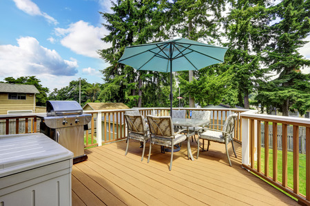 white trim: Walkout deck in brown and white trim. Patio table set with umbrella and jacuzzi Stock Photo