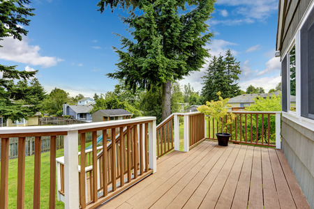 white trim: Walkout deck in brown and white trim overlooking backyard area Stock Photo