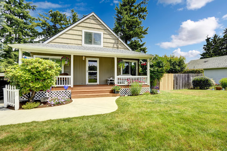 front house: House with cozy entrance porch and front yard landscape with flower bed Stock Photo