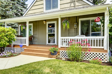 아늑한 입구 현관 집. 화이트 난간 갈색 나무 바닥과 녹색 집 외관과 조화 스톡 콘텐츠