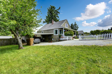 driveways: House with covered parking spot and gravel driveway Stock Photo