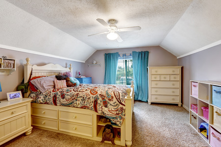 drawers: Kids room interior with vaulted ceiling. Wooden bed with drawers.