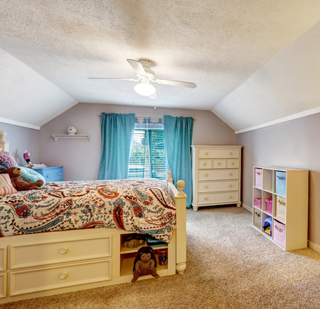 Kids room interior with vaulted ceiling. Wooden bed with drawers, studying area photo