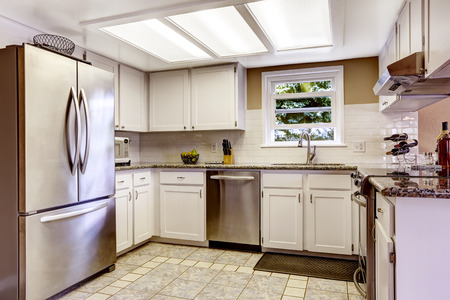 stainless steel kitchen: White kitchen room with slylight and small window. White cabinets blend with steel appliances Stock Photo