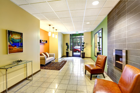 ceiling tile: Modern foyer in green, yellow and orange colors. Sitting area with wot leather chairs and fireplace Stock Photo
