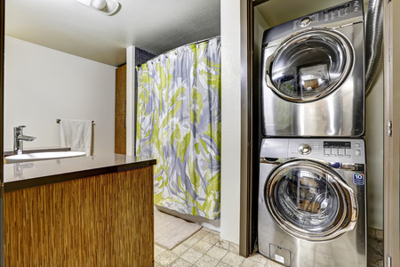 bathroom design: Bathroom with laundry room. Shiny steel washer and dryer