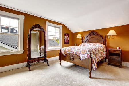 nightstand: Brown bedroom with carved wood bed, nightstand, mirror