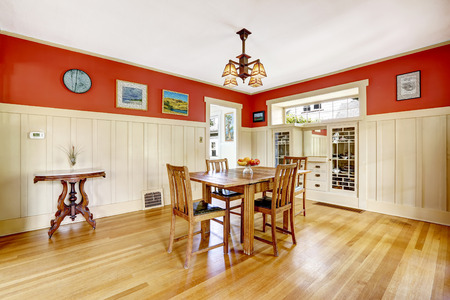 designer chair: Dining room in old house with red and white wall trim. Furnished with old wooden table set and antique small table.