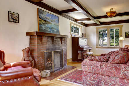 Cozy family room with antique furniture, piano and fireplace 版權商用圖片