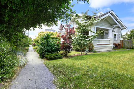 House exterior. Clapboard siding trim. View of walkway with bushes alongside photo