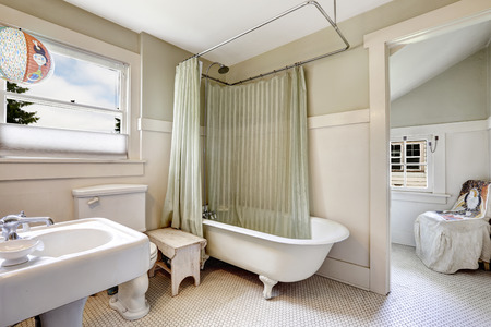 Bathroom in light green tone with white trim in old house. Claw foot tub with light green wraparound curtain.