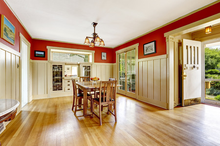 trim wall: Dining room in old house with red and white wall trim. Furnished with old wooden table set. Room has exit to backayrd area
