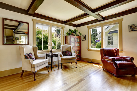 Living room with sitting area. Comfortable leather armchair and two antique chairs with small table photo