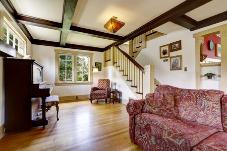 family rooms: Family room with antique piano and red sofa. Room with coffered ceiling and staircase Stock Photo