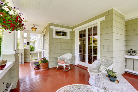 front view: Entrance porch in old house with wicker chairs and glass entrance door. Porch decorated with flower pots Stock Photo