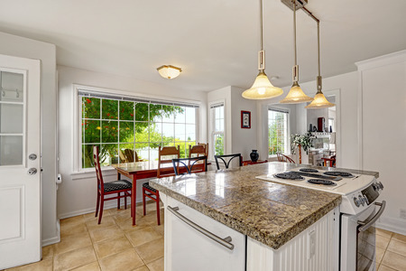 kitchen island: White kitchen room with granite tops. Kitchen island with built-in stove. View of dining area with large window