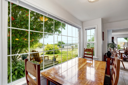 Bright dining area with large french window. Backyard view with patio area