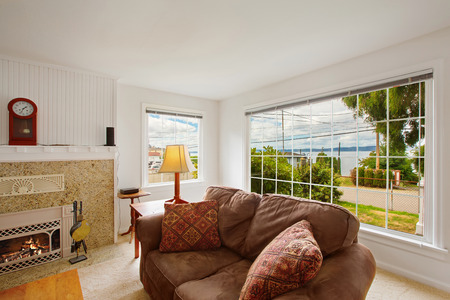 windows: Bright comfort living room with brown comfortable love seat and window view Stock Photo