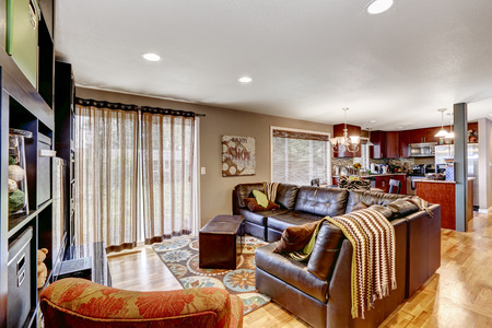 Cozy family room with leather couch bright kitchen area with burgundy cabinets