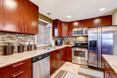Modern kitchen interior with bright wooden cabinets and steel appliances. Mosaic back splash trim blend perfectly with granite tops
