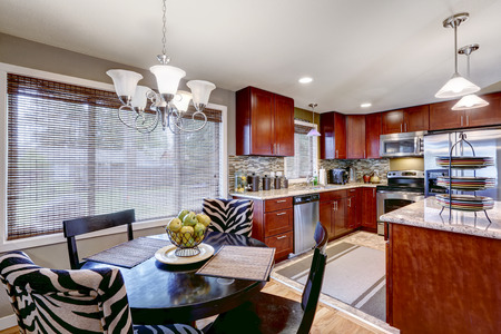 back kitchen: Modern kitchen interior with bright wooden cabinets and steel appliances. Mosaic back splash trim blend perfectly with granite tops. Black round dining table with black and zebra chairs